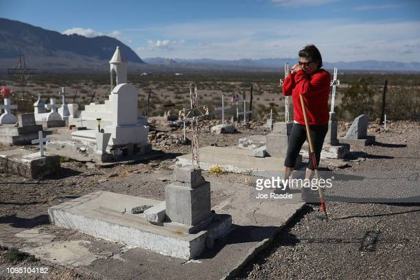 Carmen Rodriguez Luna works on cleaning up the Indio Ranch Cemetery which is on a bluff overlooking the border between the United States and Mexico...