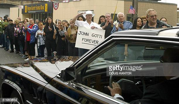 Carmine Romeo holds a sign reading John Gotti Forever and salutes the funeral procession of mob boss John Gotti in Queens New York 15 June 2002 on...