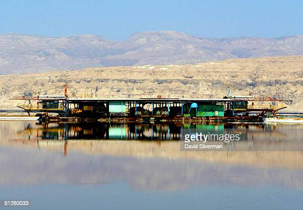 A carnalitedredgging barge floats on the mirrorlike surface of a Dead Sea Works evaporation pool at the industrial giant's potash recovery plant on...