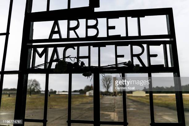 "Carnations hang at the infamous entrance gate that reads: ""Arbeit macht frei"", or ""Work sets one free"" at the Sachsenhausen concentration camp..."