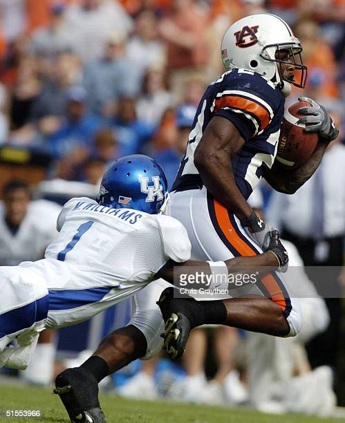 Carnell Williams of the Auburn Tigers is tackled by Mike Williams of the Kentucky Wildcats on October 23 2004 at JordanHare stadium in Auburn Alabama...