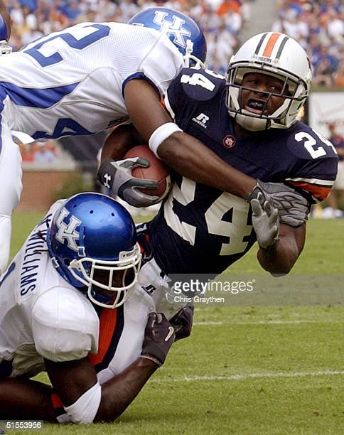 Carnell Williams of the Auburn Tigers is tackled by Mike Williams bottom and Muhammad Abdullah of the Kentucky Wildcats on October 23 2004 at...