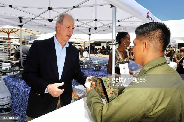 Carnival Cruise Lines Chief Maritime Officer William Burke serves hamburgers to Marines at Carnival Cruise Line's First Ever Socially Powered BBQ at...