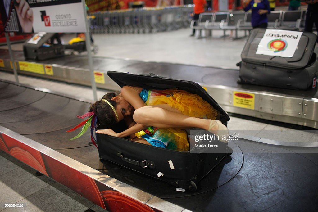 A Carnival dancer hides in a suitcase to surprise people arriving in the baggage claim area at Guararapes Gilberto Freyre International Airport on February 4, 2016 in Recife, Pernambuco state, Brazil. Officials say as many as 100,000 people may have already been exposed to the Zika virus in Recife, although most never develop symptoms. Tourists are arriving in the city for its famed Carnival celebrations which begin tomorrow.