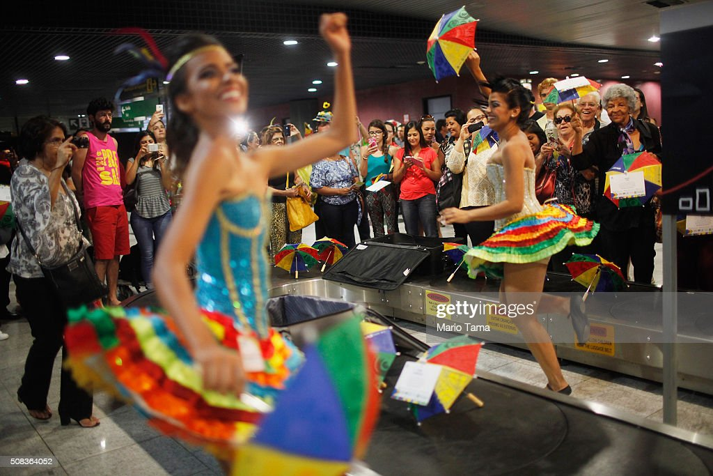 Carnival dancers perform for people arriving in the baggage claim area at Guararapes Gilberto Freyre International Airport on February 4, 2016 in Recife, Pernambuco state, Brazil. Officials say as many as 100,000 people may have already been exposed to the Zika virus in Recife, although most never develop symptoms. Tourists are arriving in the city for its famed Carnival celebrations which begin tomorrow.