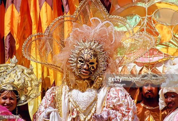 Carnival dancers wearing traditional costumes in pastel colours and gold in Trinidad Caribbean
