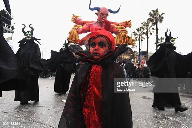 Carnival dances stand near a giant papermache float through the streets of Viareggio during the traditional Carnival of Viareggio parade on February...
