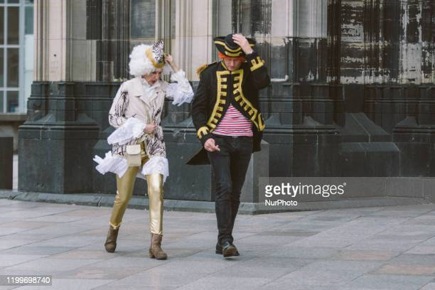 A carnival dressed couple walks against the strong wind upon the Storm Sabine arrival on February 9 2020 in Cologne Germany