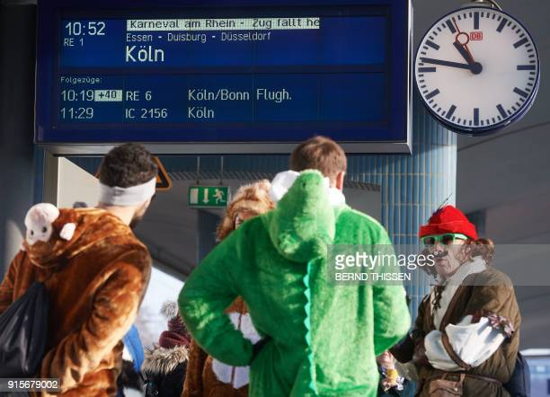 Carnival enthousiasts stand on a platform of the train station in Bochum western Germany and wait for a train to carnival stronghold Cologne on...