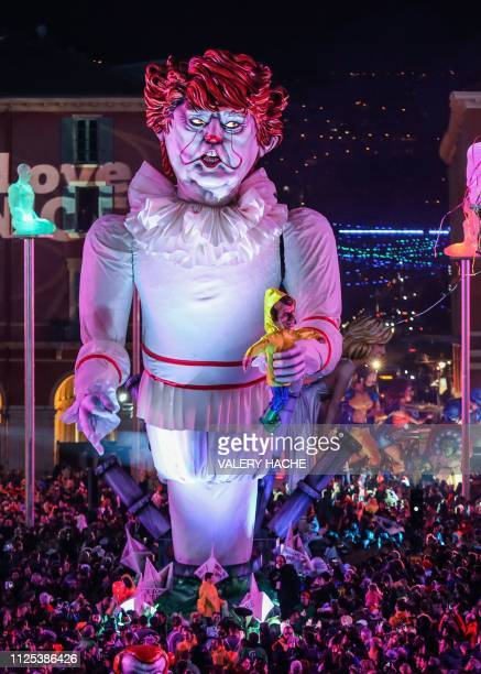 A carnival float with a giant statue of US President Donald Trump depicted as an evil clown holding a French President Emmanuel Macron's puppet in...