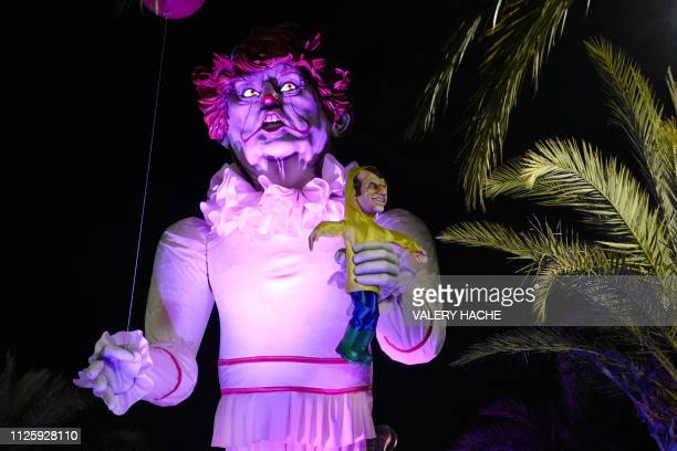 TOPSHOT A carnival float with a giant statue of US President Donald Trump depicted as an evil clown holding a French President Emmanuel Macron's...