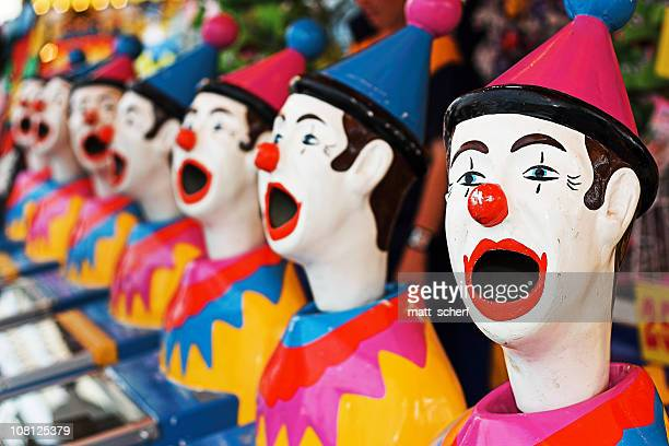 Carnival game featuring colorful open mouthed clown heads