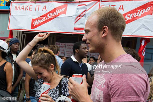 Carnival goers enjoy a Red Stripe lager at the Notting Hill Carnival on August 24 2014 in London England