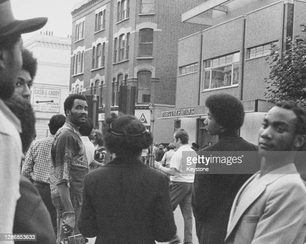 Carnival goers outside the branch of Barclays Bank on Ladbroke Grove during the Notting Hill Carnival, held across the Notting Hill district in west...