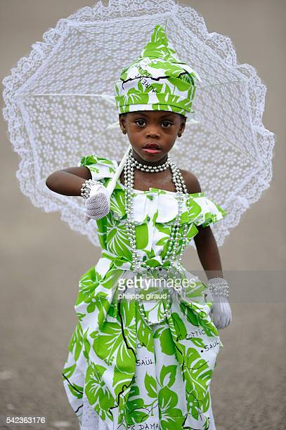 Carnival groups delight the thronging crowds with their multicolored costumes and the frenetic rhythm of their music A young girl dones a traditional...