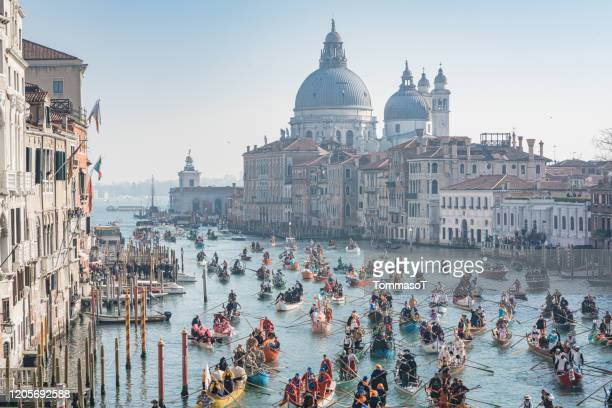 carnival of venice - carnival water parade with chiesa della salute in the background - gondola traditional boat stock pictures, royalty-free photos & images