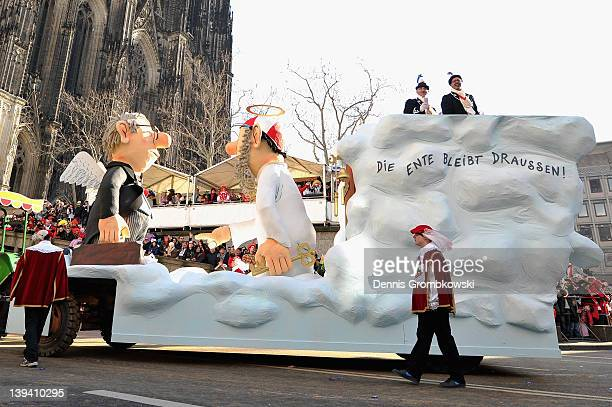 Carnival revelers accompany a float in the Rose Monday parade on February 20 2012 in Cologne Germany Rose Monday is the highpoint of the Carnival...