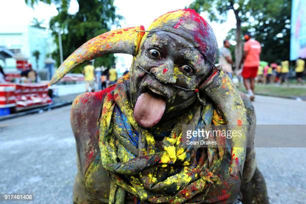 A carnival revelers with his face covered in paint and wearing horns poses for a portrair during the J'ouvert street procession as part of Trinidad...
