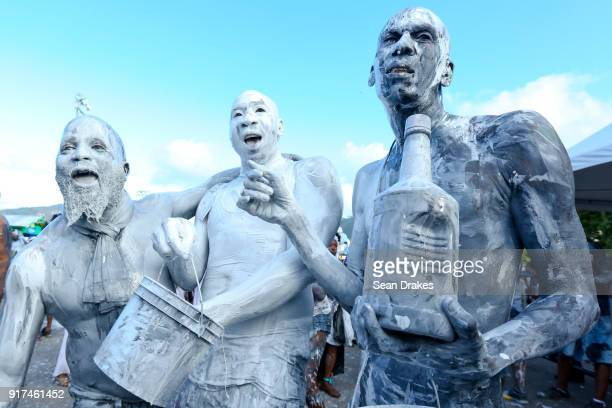 Carnival revelers with the 3Canal J'ouvert band 'Rejouvaynation' dance sing and cover their body with colored powder and paint during the J'ouvert...