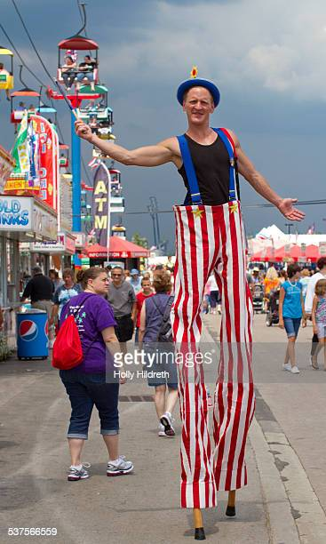 A carnival worker walks the midway on stilts at the Ohio State Fair