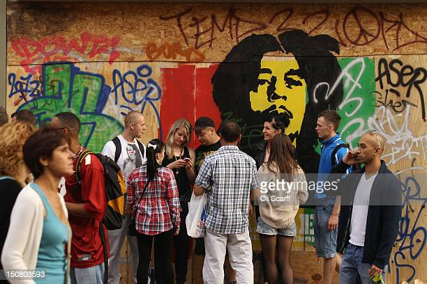 Carnivalgoers stand in front of graffiti depicting Bob Marley on the family day at the Notting Hill Carnival on August 26 2012 in London England The...
