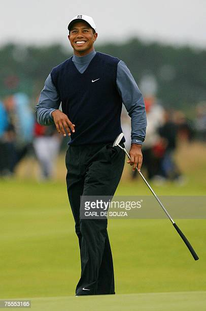 Carnoustie, UNITED KINGDOM: Defending champion Tiger Woods smiles after a birdie on the 16th hole during the first round of the 136th British Open...