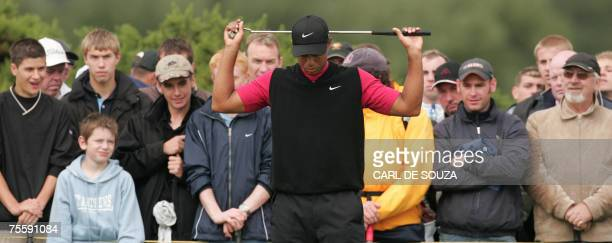 Defending champion Tiger Woods streches before hitting a shot ont he 6th hole during the final round of the 136th British Open Golf Championship at...
