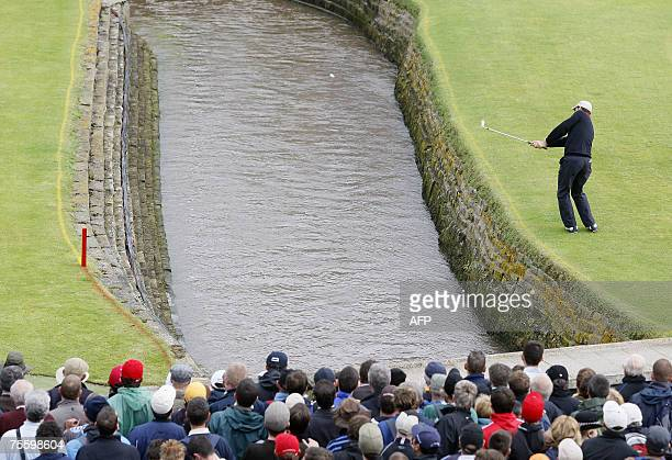 Irish Padraig Harrington chips the ball across a burn after taking a drop for playing into the water on the 18th hole during the final round of the...