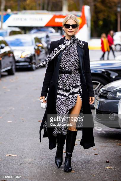Caro Daur, wearing a black and white printed dress, long black coat and black boots, is seen outside the Elie Saab show during Paris Fashion Week -...