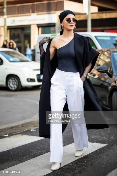 Caro Daur, wearing a black coat, white pants, sunglasses and a black shirt shoulder, is seen outside Max Mara on Day 2 Milan Fashion Week...