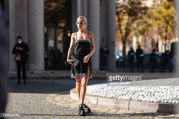 Caro Daur wearing a black dress and black shoes and a bag outside Miu Miu Show on October 05, 2021 in Paris, France.