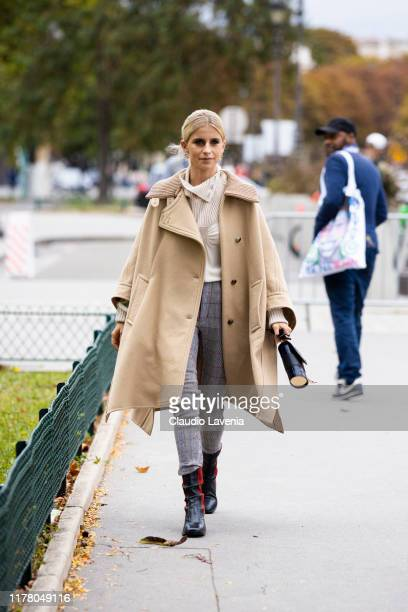 Caro Daur, wearing a cream top, checked trousers, beige coat, black Chloe bag and black and red boots, is seen outside the Chloe show during Paris...
