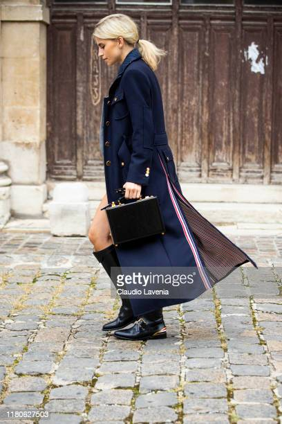 Caro Daur wearing a grey blazer with matching skirt black boots black bag and long blue coat is seen outside the Thom Browne show during Paris...