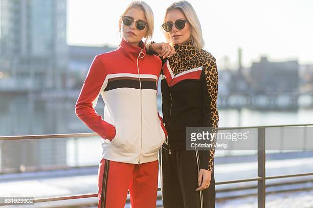 Caro Daur wearing a red track suit and Lisa Hahnbueck wearing a black track suit with leopard print during the MercedesBenz Fashion Week Berlin A/W...