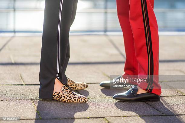 Caro Daur wearing a red track suit and Lisa Hahnbueck wearing a black track suit with leopard print and Marc Cain loafers during the MercedesBenz...