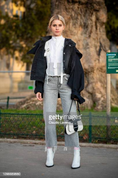Caro Daur wearing a white shirt black denim jacket grey jeans and black white boots and white Prada bag is seen in the streets of Paris before the...