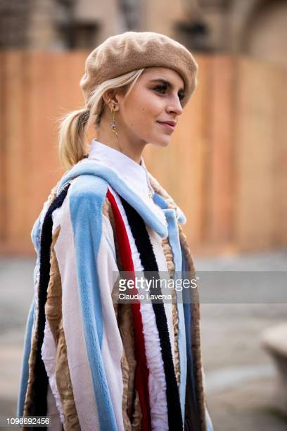 Caro Daur, wearing a white shirt, colorful striped coat and beige hat, is seen in the streets of Paris before the Thom Browne show on January 19,...
