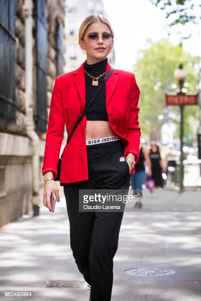 Caro Daur wearing black top red jacket and black pants is seen in the streets of Paris before the Dior Homme show during Paris Men's Fashion Week...