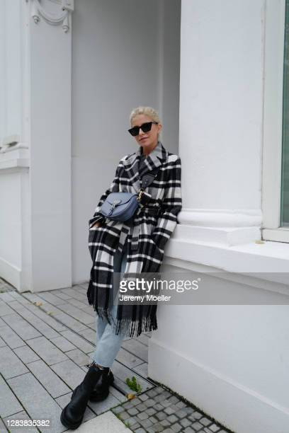 Caro Daur wearing Dior bobby bag and coat, blue jeans and black boots on October 26, 2020 in Hamburg, Germany.