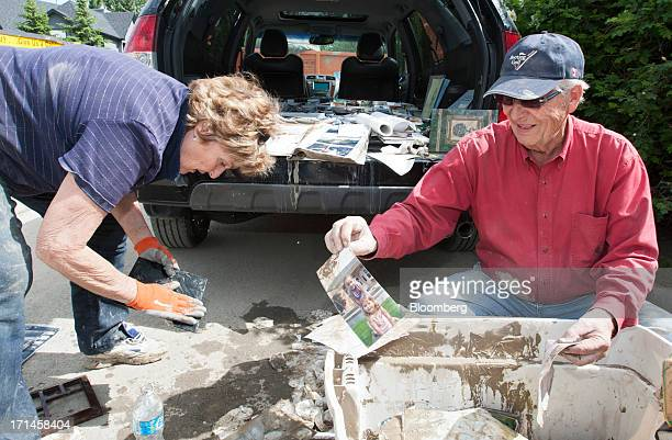Carol Armstrong left and Don Armstrong sort through waterdamaged photographs as they help clean their son's home in Rideau Park after flooding in...