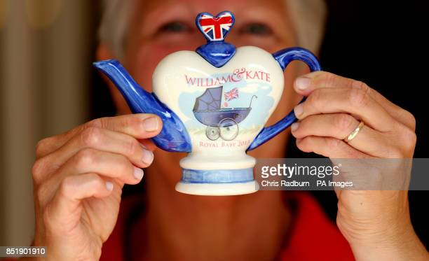 Carol Bridger of Tony Carter Ceramic Designs holds up a commemorative teapot created to celebrate the birth of Prince George of Cambridge at the...