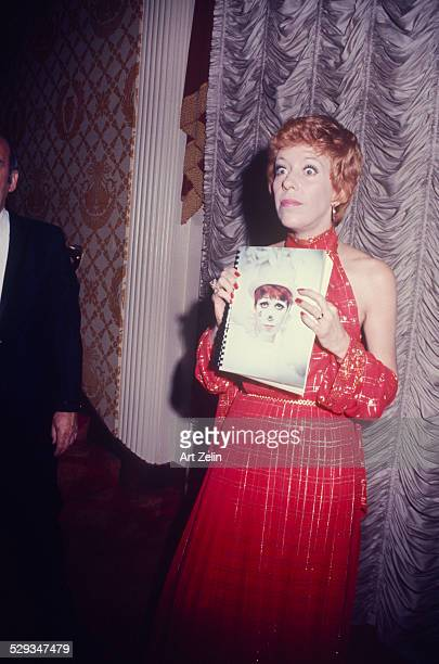 Carol Burnett in red dress with gold threads holding a picture of her as a clown circa 1970 New York