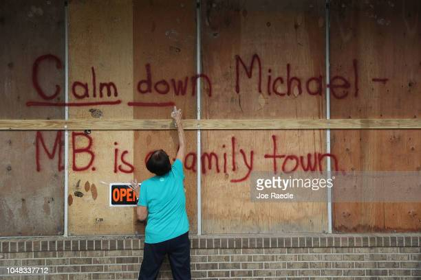 Carol Cathey spray paints the words Calm down Michael on the plywood over her daughter's business in preparation for the arrival of Hurricane Michael...