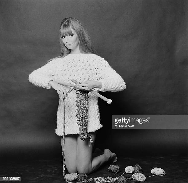 Carol Christopher models a long white knitted sweater called 'Long Island' whilst knitting with maxipins UK 2nd November 1967
