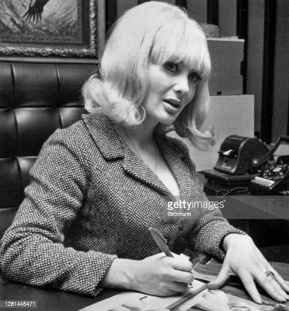 Carol Doda, star of the Condor Club revue, who was escorted around new York City by Jet's star quarterback Joe Namath, autographs photos she's...