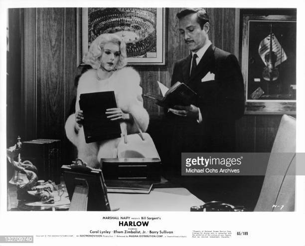 Carol Lynley and Barry Sullivan standing in office together in a scene from the film 'Harlow' 1965