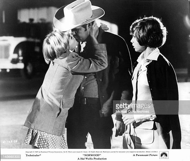 Carol Lynley grabs Glen Campbell and kisses him as Kim Darby stands as the third wheel watching them in a scene from the film 'Norwood' 1969