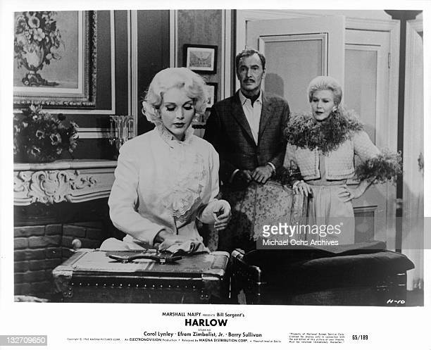 Carol Lynley handling her luggage while Barry Sullivan and Ginger Rogers watch in a scene from the film 'Harlow' 1965
