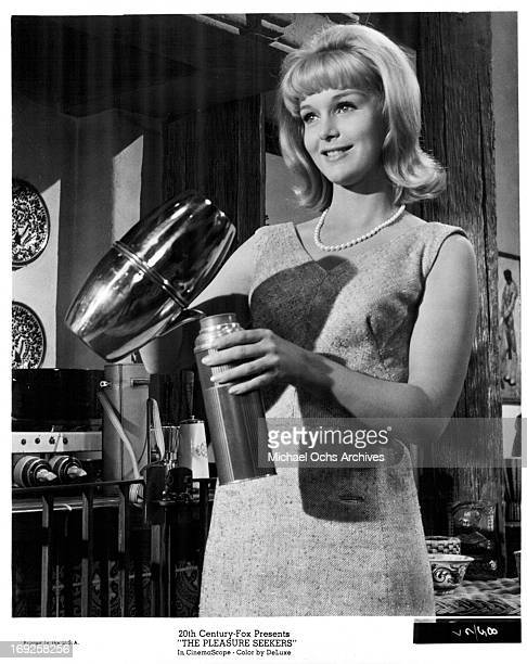 Carol Lynley pours a drink in a scene from the film 'The Pleasure Seekers' 1964