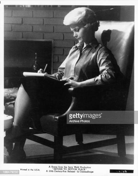 Carol Lynley sitting in a chair writing on a tablet of paper in a scene from the film 'Return To Peyton Place' 1961